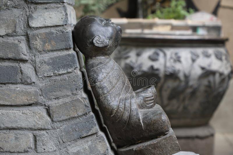 UÅ›miechniÄ™ty, maÅ'y, kamienny posÄ…g Buddy obok wrót księżyca, spokojny i inkluzywny zdjęcie royalty free