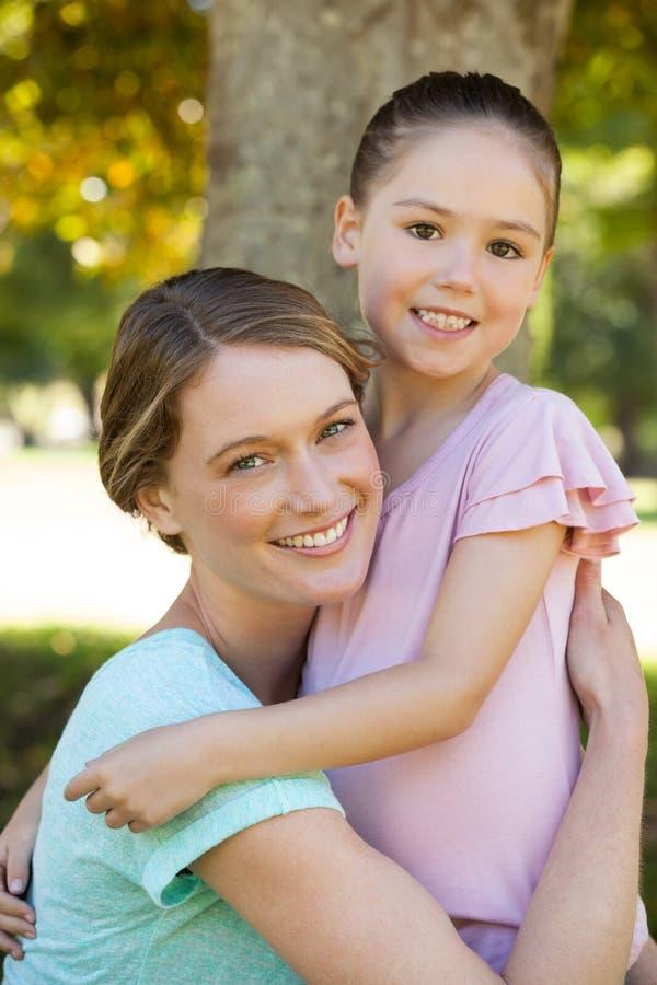 Uśmiechnięty macierzysty obejmowanie jej córka przy parkiem zdjęcia stock