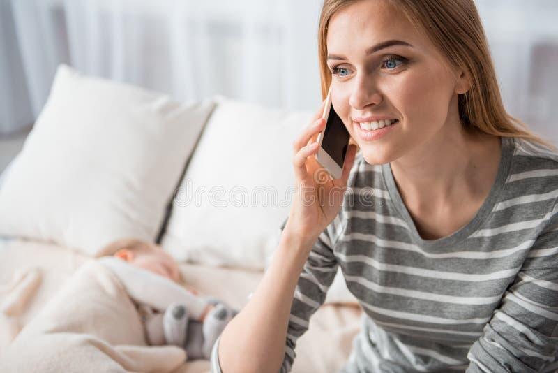 Uśmiechnięty macierzysty opowiadać na telefonie komórkowym zdjęcie stock