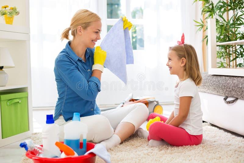 Uśmiechnięty matki i dzieciaka cleaning pokój obraz stock