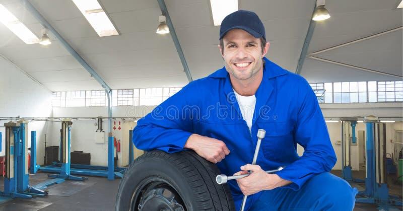Uśmiechnięty mechanik opiera na oponie obraz royalty free