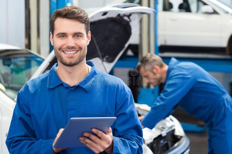 Uśmiechnięty mechanik używa pastylka komputer osobistego zdjęcie stock