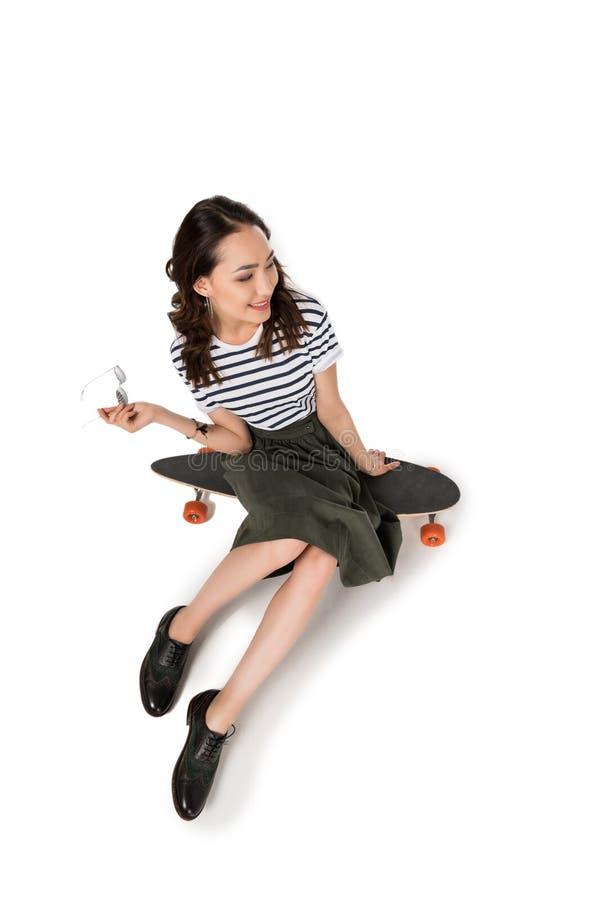 Uśmiechnięty modniś dziewczyny obsiadanie na deskorolka i patrzeć daleko od fotografia royalty free