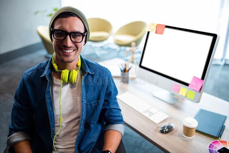 Uśmiechnięty modnisia biznesmen pozuje dla kamery podczas gdy siedzący przy biurkiem zdjęcie stock