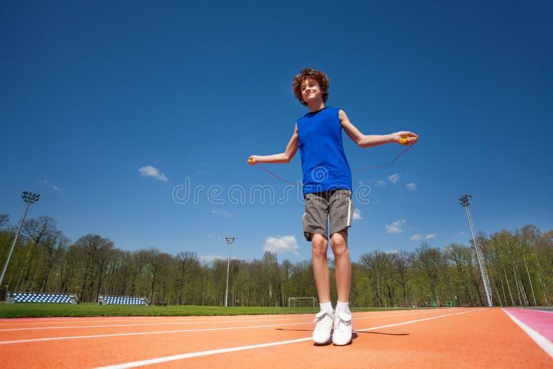 Uśmiechnięty nastoletni chłopak skacze linowego outside zdjęcie stock