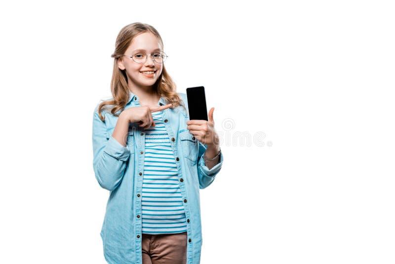 Uśmiechnięty nastoletniej dziewczyny mienia smartphone i wskazywać z palcem przy pustym ekranem obraz stock