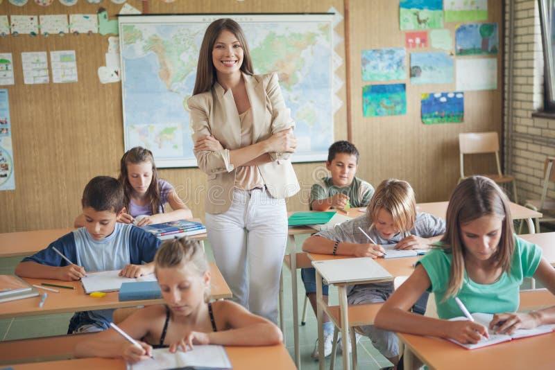 Uśmiechnięty nauczyciel i Jej ucznie zdjęcie royalty free