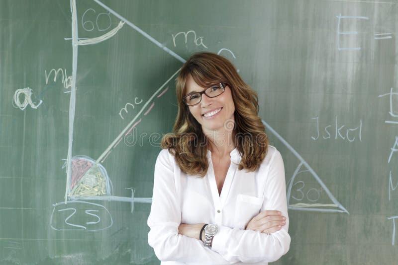 Uśmiechnięty nauczyciel przed blackboard obrazy royalty free