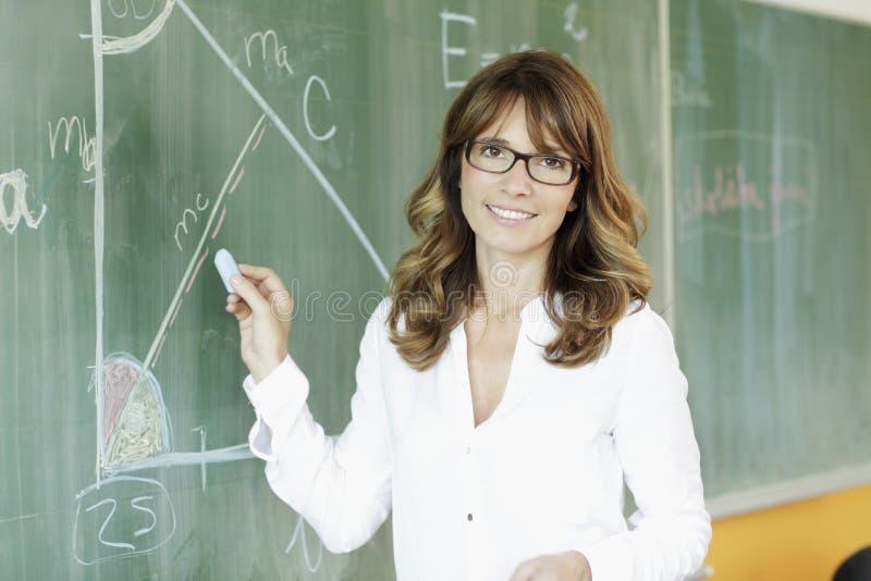 Uśmiechnięty nauczyciel przed blackboard zdjęcie stock