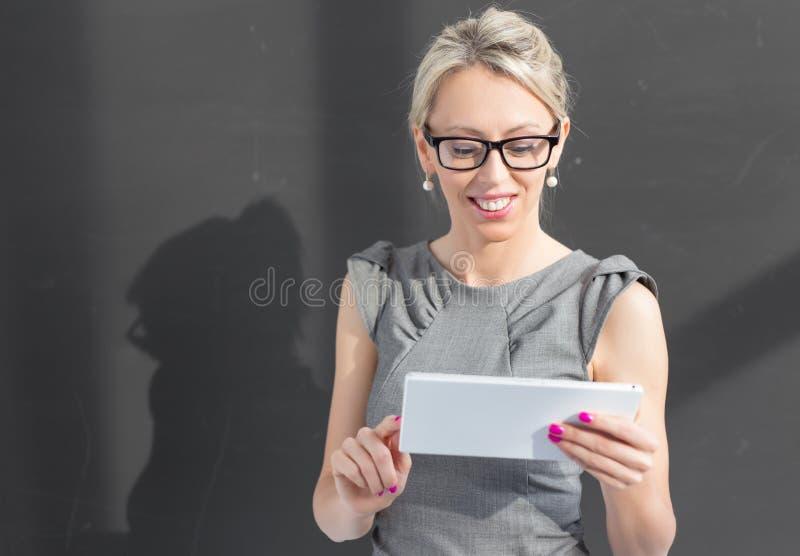 Uśmiechnięty nauczyciel używa pastylka komputer fotografia stock