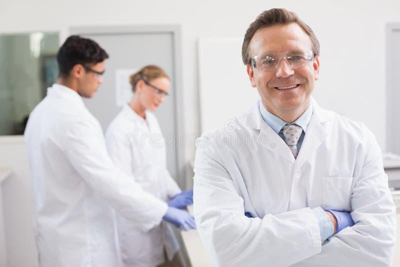 Uśmiechnięty naukowiec patrzeje kamerę podczas gdy koledzy pracuje behind fotografia stock
