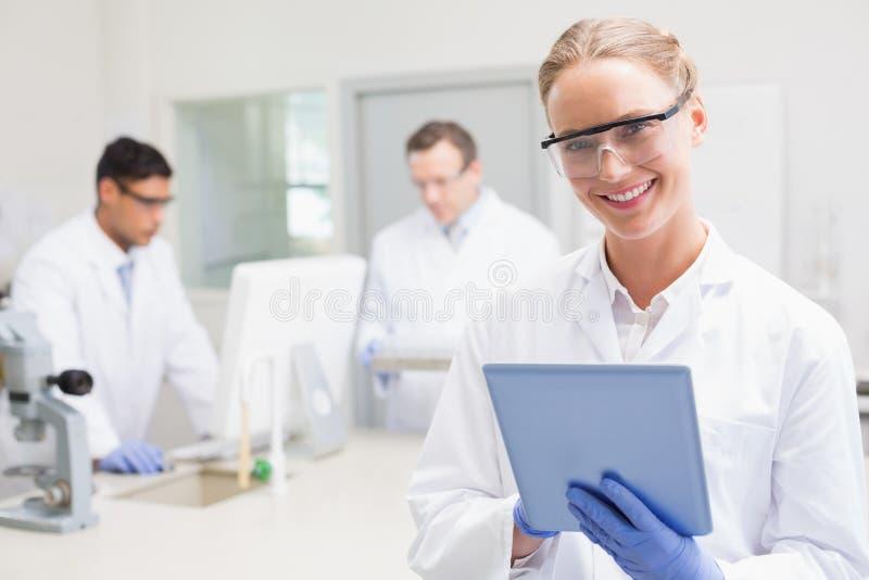 Uśmiechnięty naukowiec używa pastylkę podczas gdy koledzy pracuje behind obraz royalty free