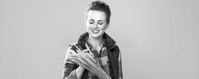 Uśmiechnięty nowożytny kobieta hodowca obserwuje pszenicznych spikelets obrazy royalty free