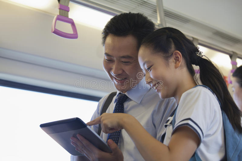 Uśmiechnięty ojciec i córka ogląda film w metrze na cyfrowej pastylce fotografia stock
