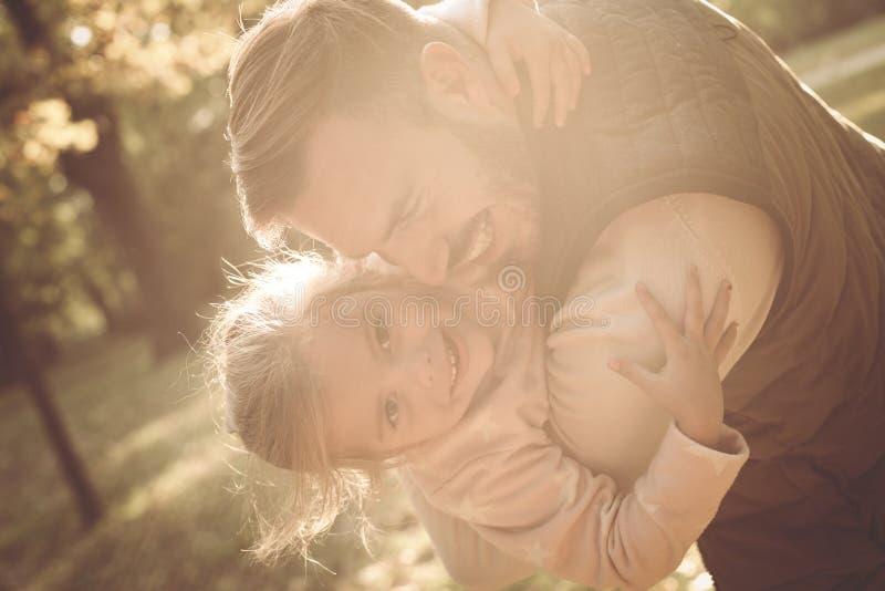 Uśmiechnięty ojciec i jego małej dziewczynki kursowanie w parku wpólnie obrazy royalty free