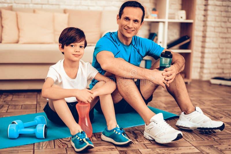 Uśmiechnięty ojciec i syn Odpoczywamy po Trenować w domu zdjęcia stock