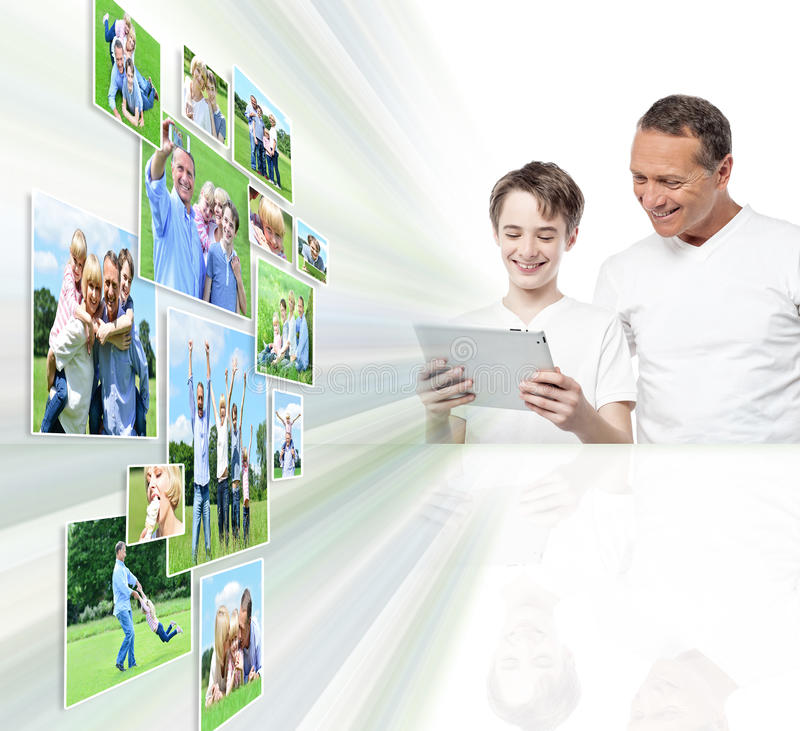 Uśmiechnięty ojciec i syn patrzeje obrazki zdjęcie royalty free