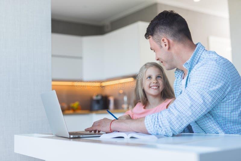 Uśmiechnięty ojciec z córką robi pracie domowej zdjęcia stock