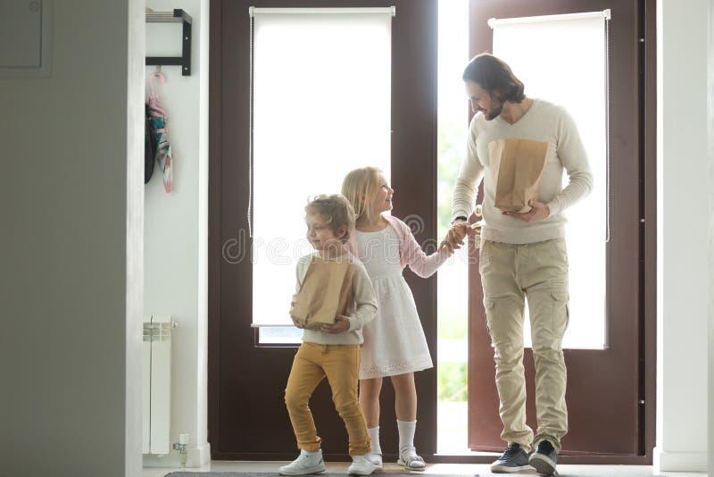 Uśmiechnięty ojciec z dzieciakami przychodzi z powrotem domowego mienia papierowe torby zdjęcia stock