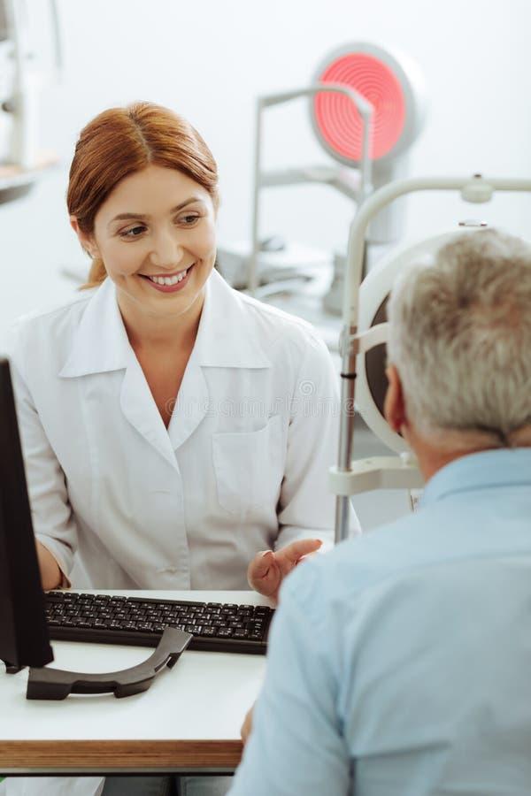 Uśmiechnięty oko specjalisty czuć dobry podczas gdy konsultujący przechodzić na emeryturę mężczyzny zdjęcie stock