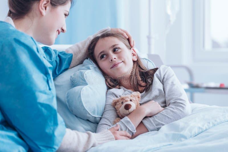 Uśmiechnięty opiekun odwiedza szczęśliwej, chorej dziewczyny w centrum zdrowia, zdjęcie stock