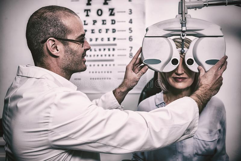 Uśmiechnięty optometrist egzamininuje żeńskiego pacjenta na phoropter zdjęcia stock