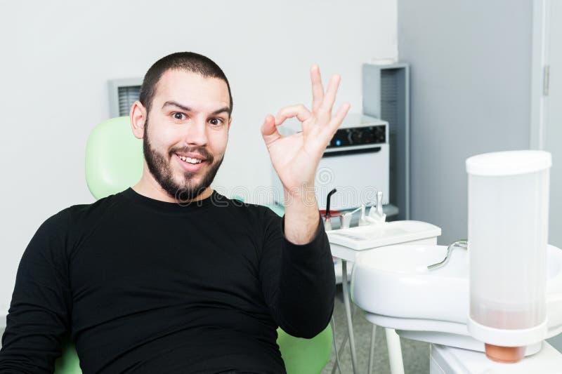 Uśmiechnięty pacjent przy dentysty seansem zatwierdza gest lub doskonalić zdjęcia royalty free