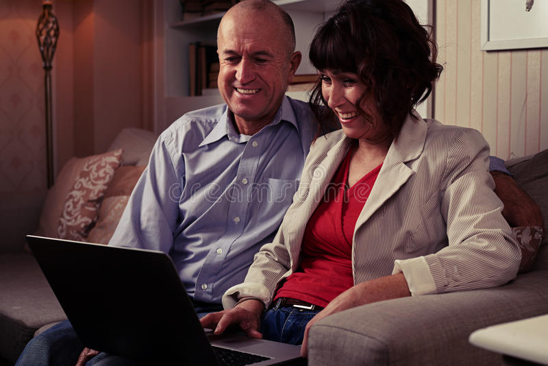 Uśmiechnięty pary obsiadanie na kanapie indoors ogląda w laptopie fotografia stock