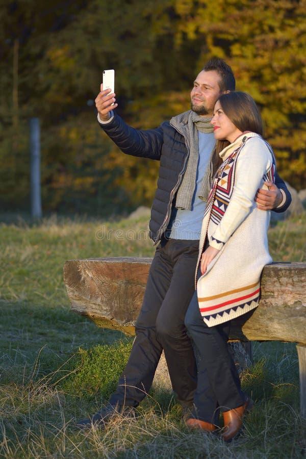 Uśmiechnięty pary przytulenie i brać selfie w jesień parku obraz stock