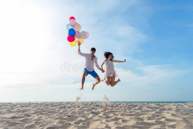Uśmiechnięty pary ręki mienia balon, doskakiwanie i gratulacyjny skalowanie w Szczęśliwym nowym roku 2019 na plaży wpólnie obrazy stock