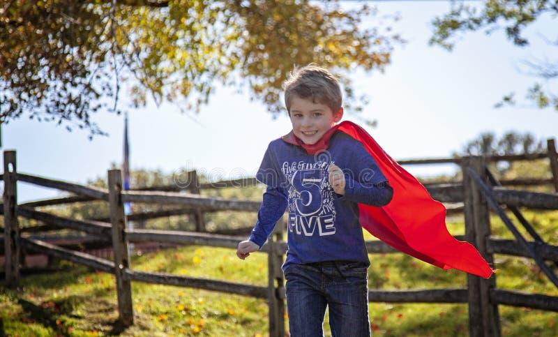 Uśmiechnięty pięcioletni stary chłopiec bieg z czerwonym przylądkiem outside fotografia stock