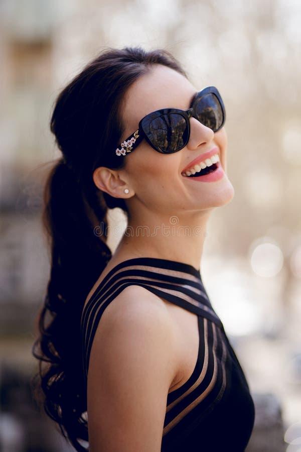 Uśmiechnięty piękny brunetka model w eleganckich czerń smokingowych i modnych okularach przeciwsłonecznych, ponytail, pozować out zdjęcie royalty free
