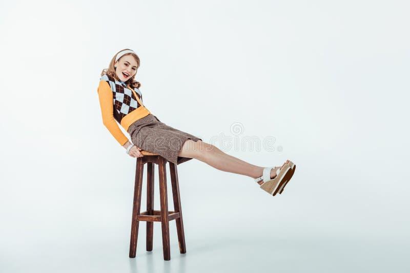 uśmiechnięty piękny retro projektujący dziewczyny obsiadanie na drewnianym krześle i patrzeć kamerę obraz stock