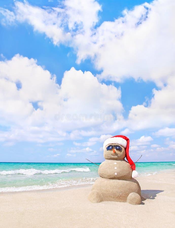 Uśmiechnięty piaskowaty bałwan w czerwonym Santa kapeluszu na dennej plaży fotografia stock