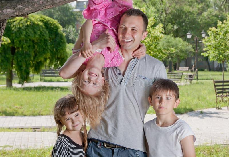 Uśmiechnięty potomstwo ojciec z jego dziećmi fotografia stock