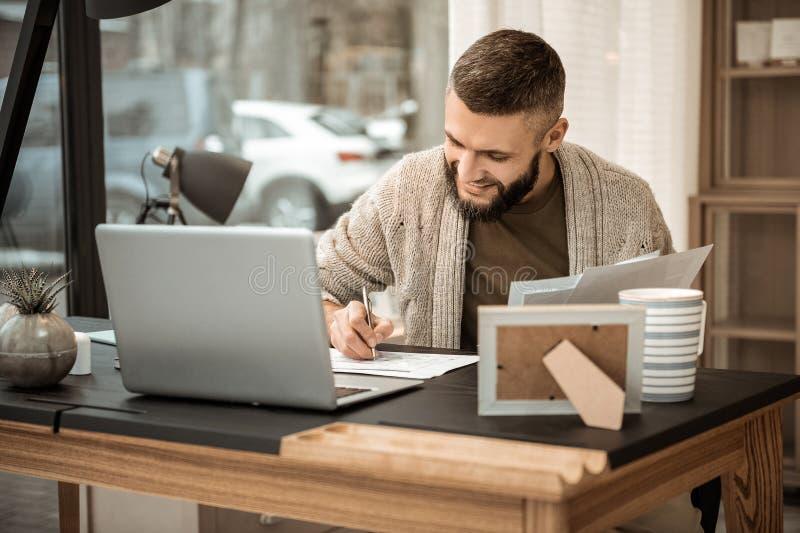 Uśmiechnięty pozytywny biznesowy mężczyzna pisze puszka spotykać w popielatym kardiganie fotografia stock