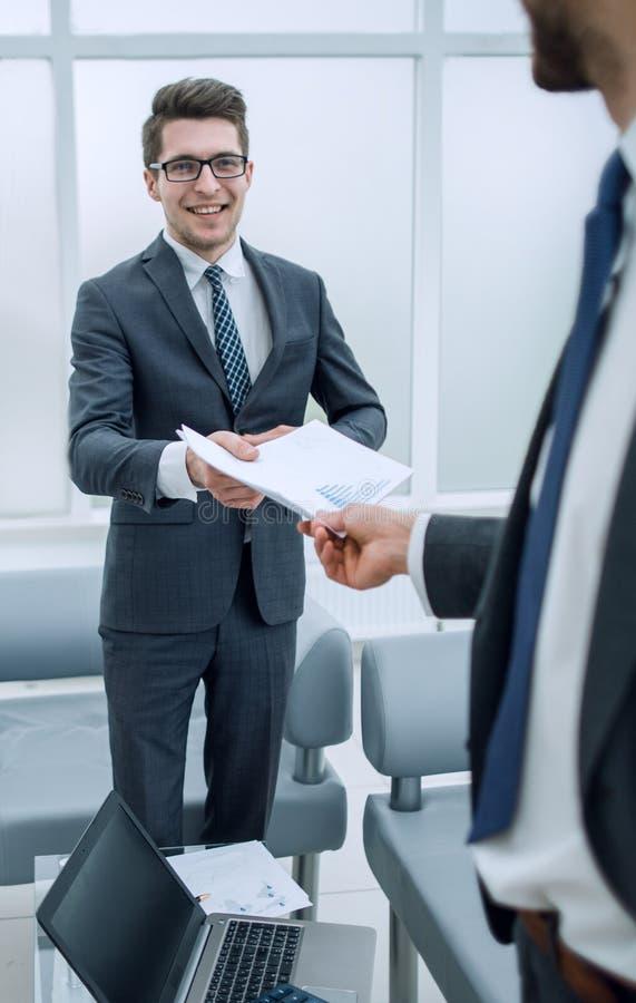 Uśmiechnięty pracownik, daje raportowi na kierowniku projektu zdjęcie royalty free