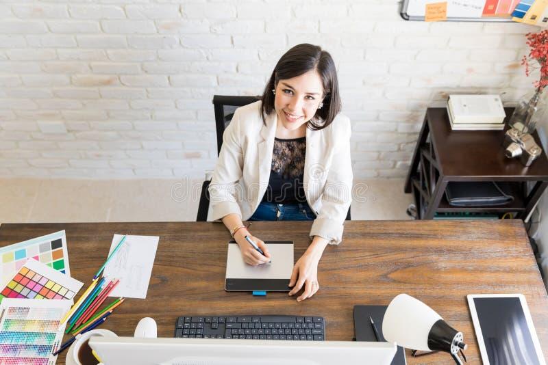 Uśmiechnięty projektant grafik komputerowych przy jej biurkiem obrazy stock