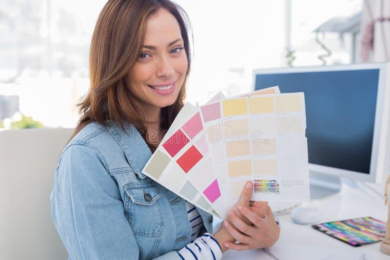 Uśmiechnięty projektant wnętrz trzyma up colour próbki fotografia stock