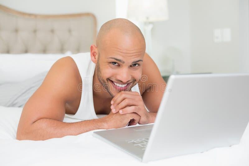 Uśmiechnięty przypadkowy łysy mężczyzna używa laptop w łóżku fotografia stock