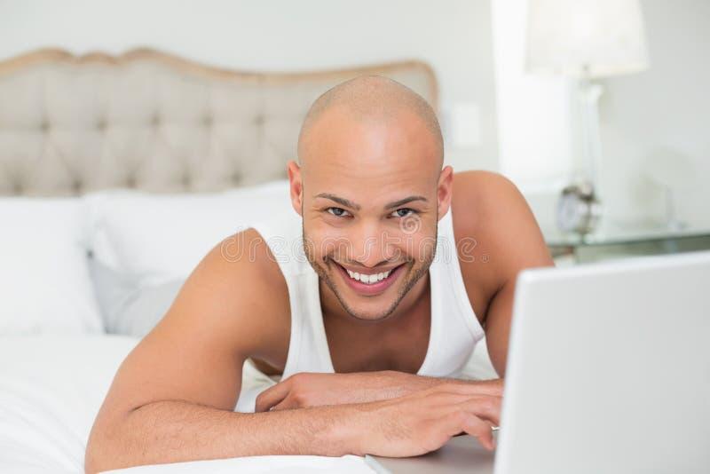 Uśmiechnięty przypadkowy łysy młody człowiek używa laptop w łóżku obraz royalty free