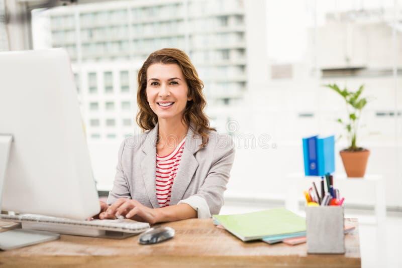 Uśmiechnięty przypadkowy bizneswoman pracuje z komputerem fotografia stock