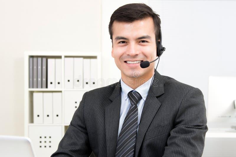 Uśmiechnięty przystojny biznesmen jest ubranym mikrofon słuchawki zdjęcia stock
