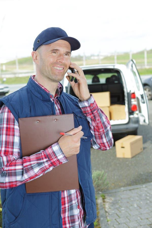 Uśmiechnięty przystojny doręczeniowego mężczyzna mienia pudełko i robić wezwanie fotografia stock