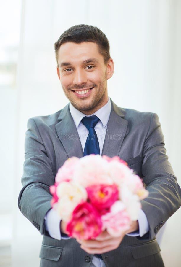 Uśmiechnięty przystojny mężczyzna daje bukietowi kwiaty obraz royalty free