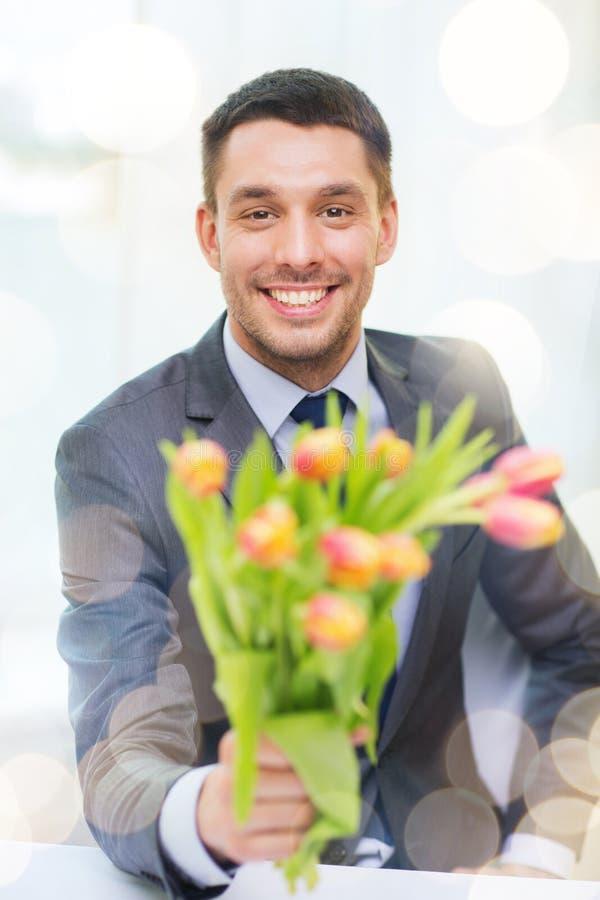 Uśmiechnięty przystojny mężczyzna daje bukietowi kwiaty fotografia stock