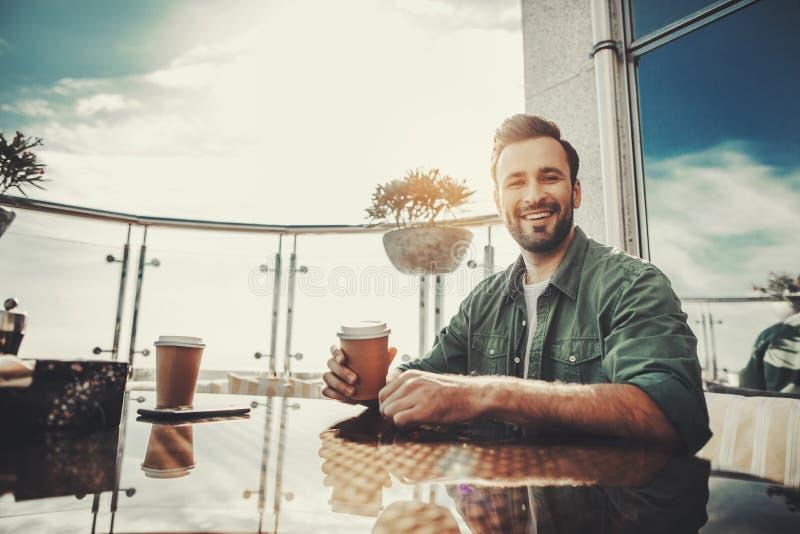 Uśmiechnięty przystojny mężczyzna przy plenerową kawiarnią zdjęcia stock