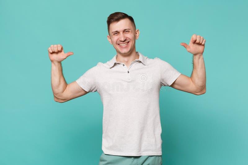 Uśmiechnięty przystojny młody człowiek stoi w przypadkowych ubraniach, wskazuje kciuki na on odizolowywałem na błękitnej turkus ś zdjęcie stock