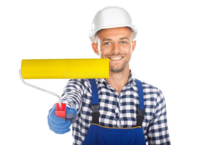Uśmiechnięty przystojny malarz z farba rolownikiem odizolowywającym na białym bac zdjęcie royalty free
