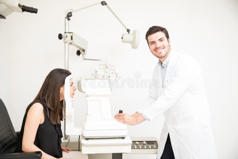 Uśmiechnięty przystojny okulista sprawdza młodych kobiet oczy obraz royalty free